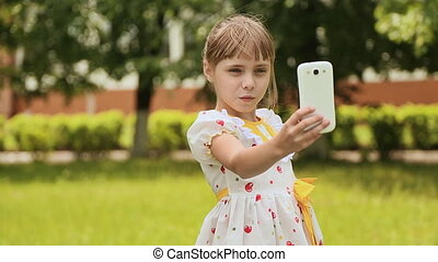 Little girl in a white dress makes selfi on the meadow.