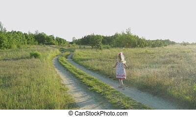 little girl in a white sundress with red patterns running across the field