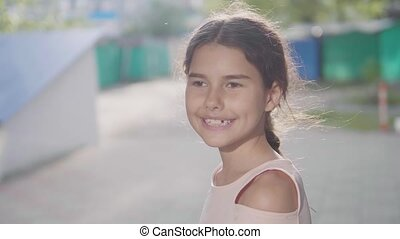 Little girl in an urban setting smiles at the camera...