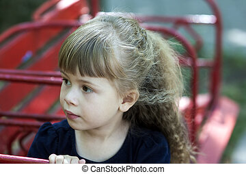 Little girl in an urban setting smiles at the camera. Portrait of happy, positive, smiling, playful  caucasian girl with beautilul hair.