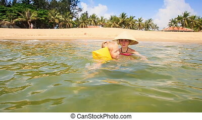 Little Girl in Armbands Swims from Mother to Azure Sea