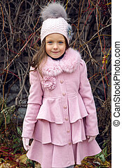 little girl in autumn leaves and pink coat