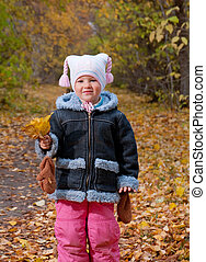 Little girl  in autumn park.