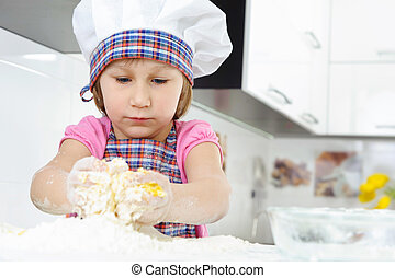 Little girl in baker hat cooking