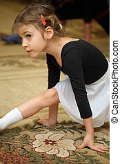 little girl in ballet class sits on string on floor with...