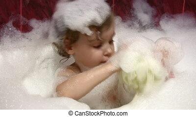 little girl in bath with bast wisp