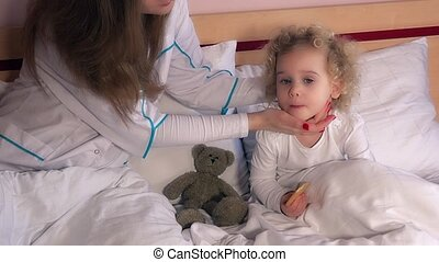 Little girl in bed having health check pediatrician doctor check head and throat