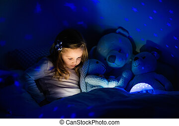 Little girl in bed with night lamp - Little girl reading a...