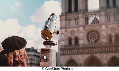 Little girl in beret looks through coin telescope. Slow...