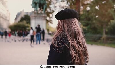 Little girl in beret stands alone on city square. Back view....