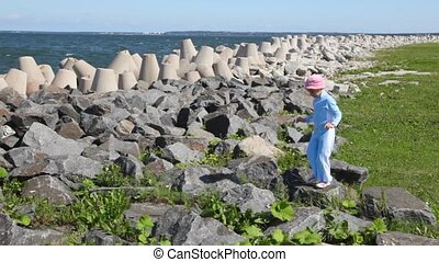little girl in blue and pink cap jumps on stones on seashore