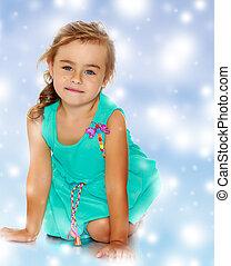 Little girl in blue dress on her knees