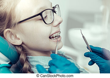 Little girl in braces sitting in a dental chair