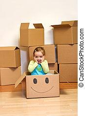 Little girl in cardboard box - moving concept - Little girl...