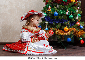 little girl in carnival costume holding Christmas ball