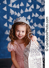 Little girl in christmas decorations. Portrait of Beautiful little girl with long curly hair with crown.