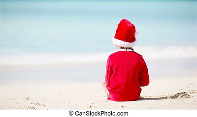 Little girl in Christmas hat on white beach during Xmas vacation
