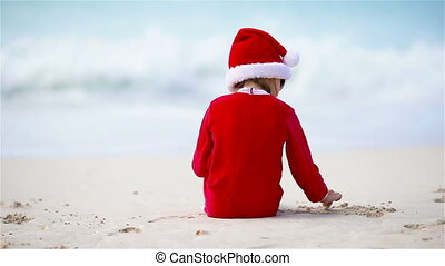 Little girl in Christmas hat on white beach during Xmas...