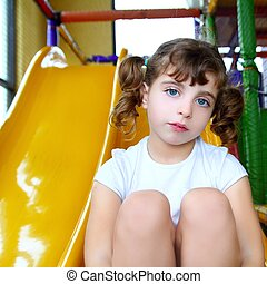 little girl in colorful playground yellow slide