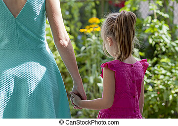 Little girl in dress holding a hand of her mother