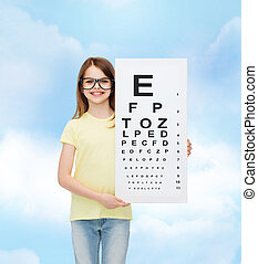 little girl in eyeglasses with eye checking chart
