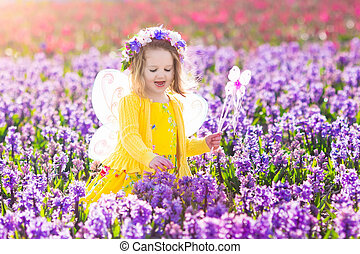 Little girl in fairy costume playing in flower field