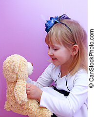 Little girl in fashionable hat play with toy bear cub in hands smiling