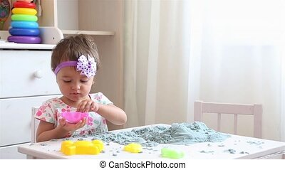 Little girl in floral dress at white table playing with ...