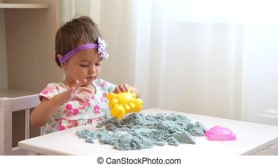 Little girl in floral dress plays with conical sand HD - ...