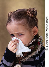Little girl in flu season - wearing warm clothes and blowing nose