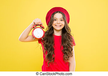 little girl in french style hat. beauty hairdresser and fashion. child with alarm clock. Timeless fashion. parisian child. happy girl with long curly hair in beret. fashion is fleeting. fashion time