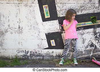 Little girl in front of graffiti wall