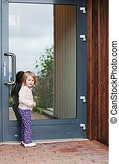 Little girl in front of the door