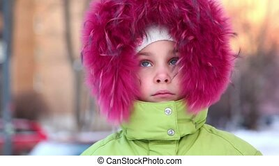 Little girl in fur hood buttoned at collar, look at camera