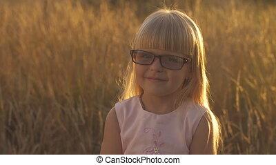 Little girl in glasses at sunset