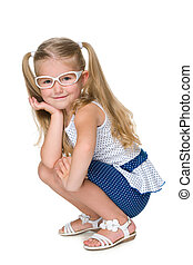Little girl in glasses is sitting against the white
