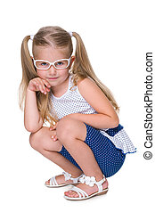 Little girl in glasses sits on the floor