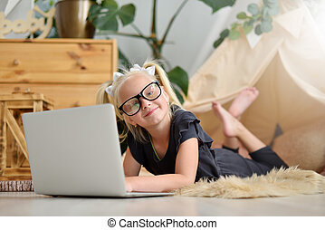 Little girl in glasses with laptop on the floor in her room