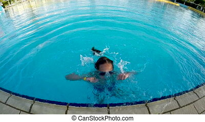 Little girl in goggles jumping playing in pool gesturing...