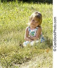 Little Girl in grass - a cute little girl is sitting in the ...