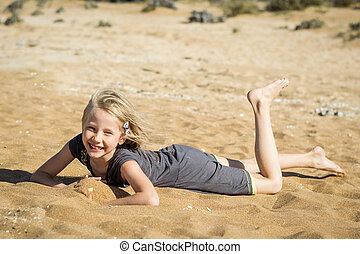 Little girl in gray dress is resting on the hot sand.