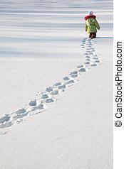 little girl in green jacket walking on snow, footprints in snow, behind