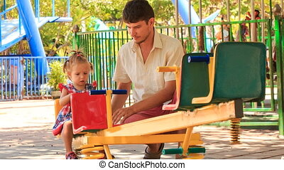 little girl in hairtails tries to climb up on swing father helps