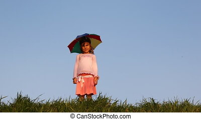 Little girl in hat as rainbow umbrella turns on grass