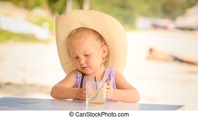 Little Girl in Hat Drinks Juice with Spoon from Glass