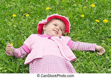 little girl in hat lying on the lawn