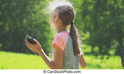 Little girl in headphones listening to the music outdoors.