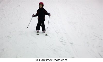 Little girl in helmet and warm clothes moves alpine skis
