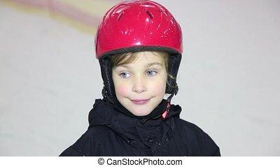 Little girl in helmet looks and smiles, mother moves on ski