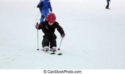 Little girl in helmet moves ski poles on alpine skis
